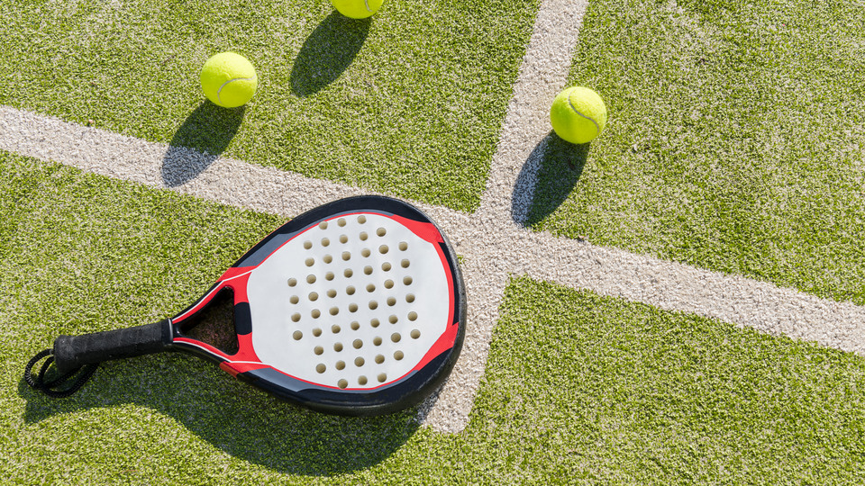top view of a paddle tennis racket and balls on court of artificial grass, indoor sports concept and sporty lifestyle